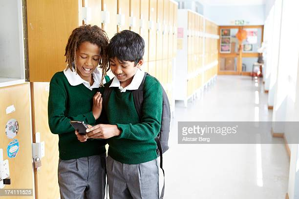 Boys playing on a cell phone at school