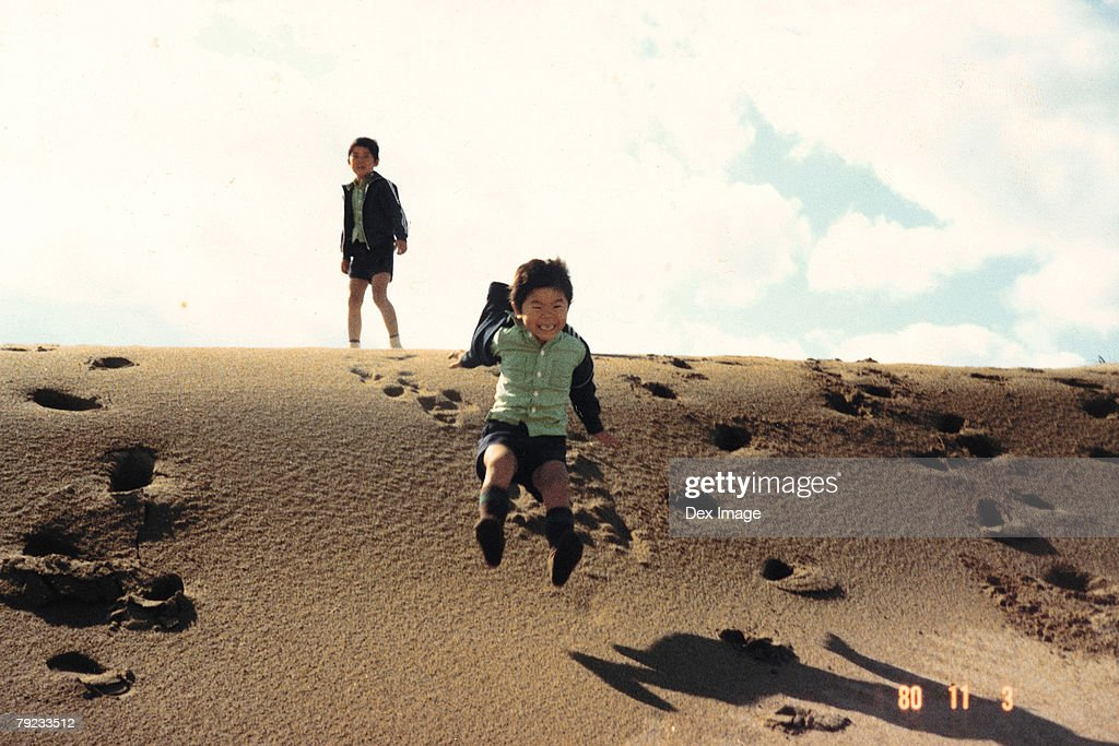 Boys playing on a sandy slope : Stock Photo