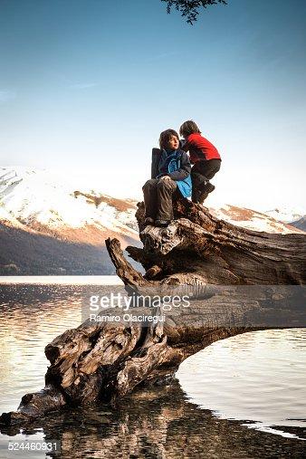 Boys playing on a tree, lake at sunset