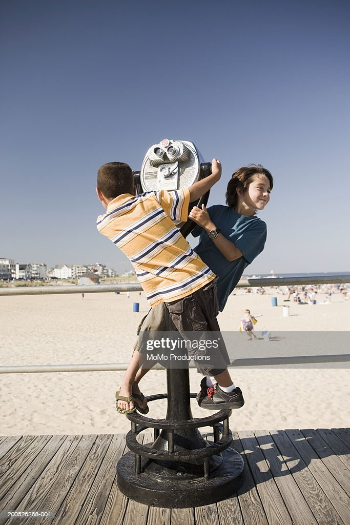 Boys (5-9) playing on boardwalk viewer, side view : Stock Photo
