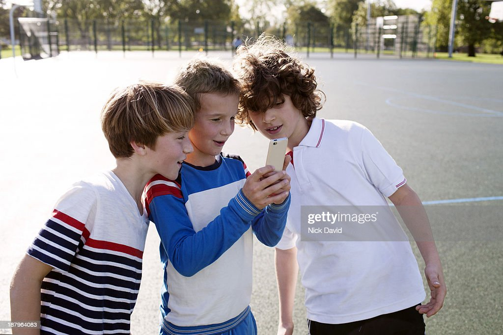 Boys playing outside using mobile phone : Stock Photo