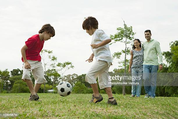 Boys playing soccer, parents watching in background