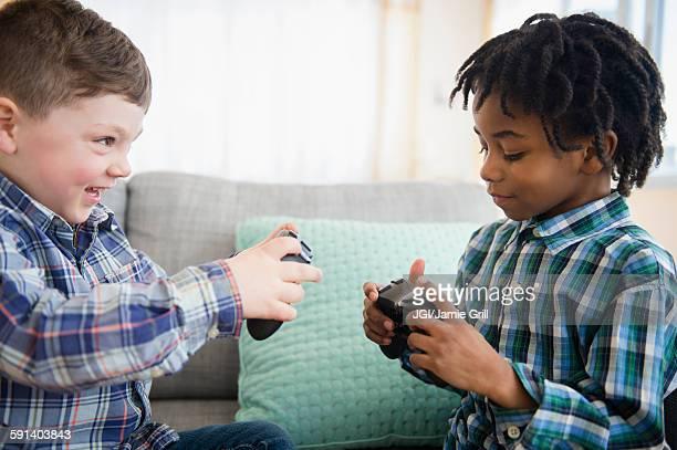 Boys playing video games on sofa