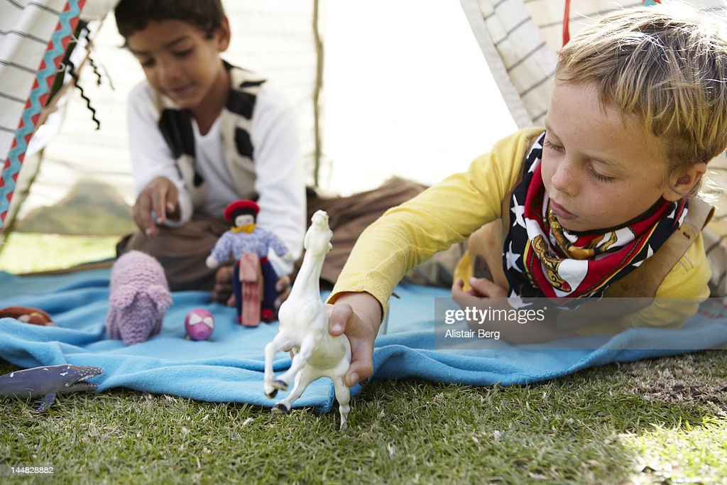 Boys playing with animals in a tent : Stock Photo