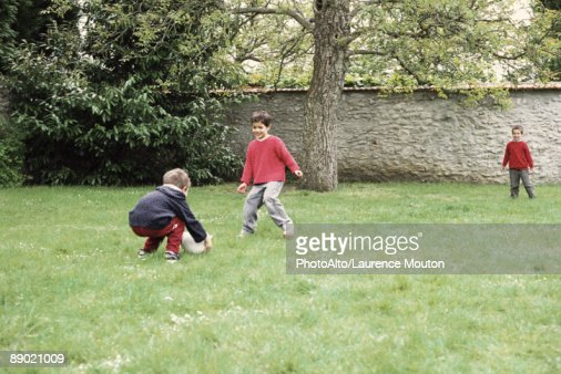 Boys playing with ball in yard