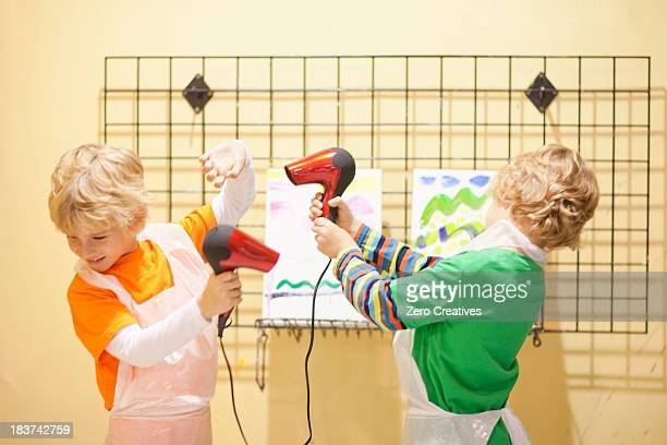 Boys playing with hair dryers whilst drying their paintings