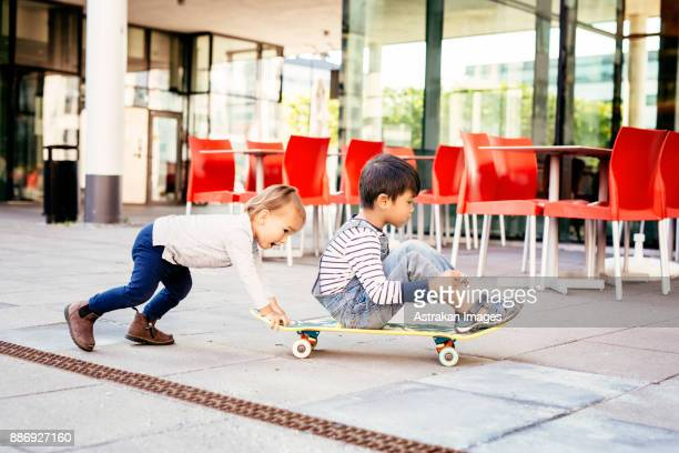 Boys (2-3, 4-5) playing with skateboard
