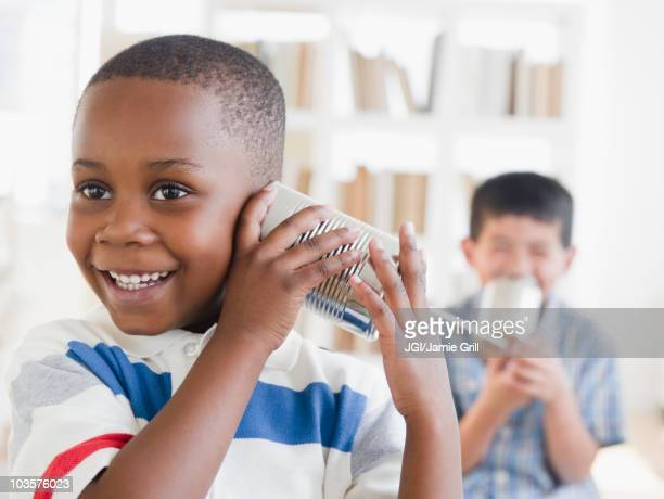 Boys playing with tin can telephone