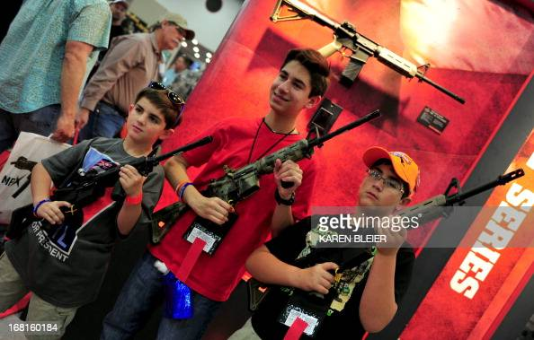 Boys pose for a photo holding Bushmaster rifles during the 142nd annual National Rifle Association convention at the George R Brown Convention Center...