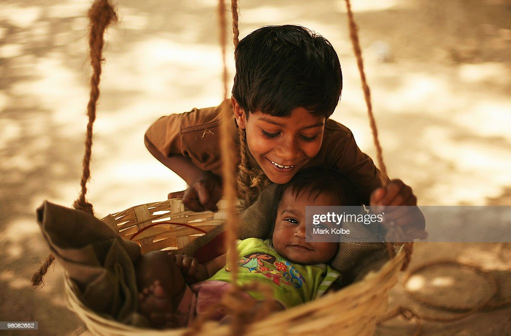 A boys poses with his baby sister as she swings in a hanging basket in sector 22 market place on March 27, 2010 in Chandigarh, India.