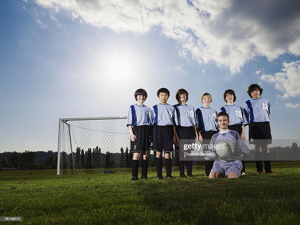Boys (10-11, 11-12) posing in front of goal, team portrait : Stock Photo