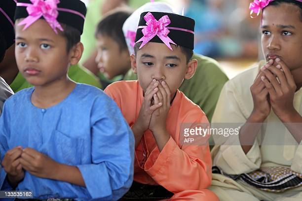 Boys pray during a ceremony before they are circumcised in Kajang outside Kuala Lumpur on November 20 2011 About 30 boys aged between 7 and 11 who...