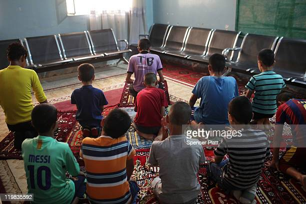 Boys pray in the AlBaraum orphanage on July 25 2011 in Baghdad Iraq The state owned orphanage has about 50 children currently with the number...