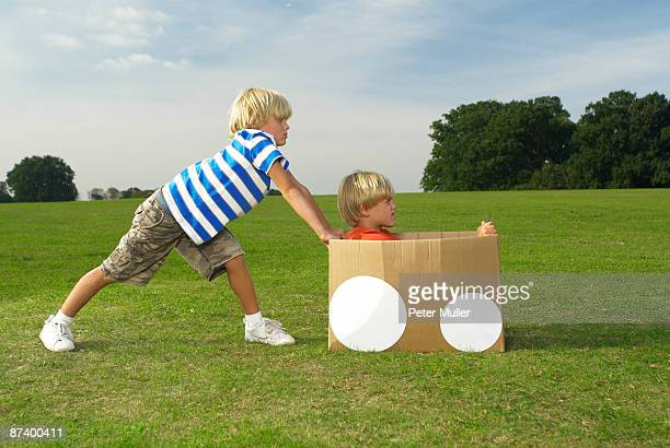 boys pushing another boy in box