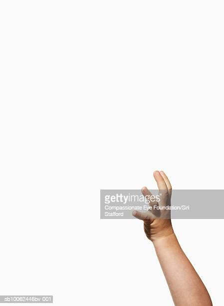 Boy's (2-3) raised arm against white background