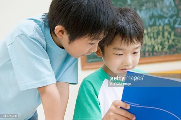 Boys reading book in classroom