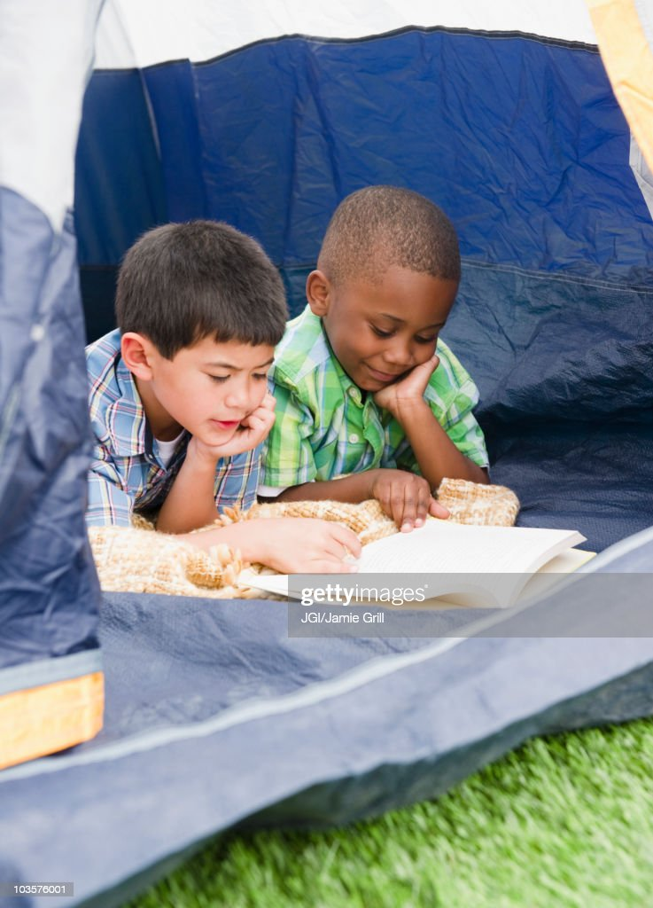 Boys reading book in tent : Stock Photo