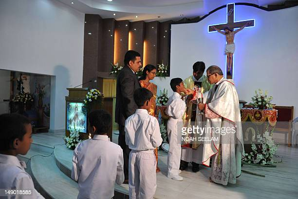 Boys receive their First Holy Communion from Indian Catholic Archbishop Thumma Bala at the Mount Caramel Church in Hyderabad on July 22 2012 First...