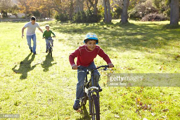 Boys riding bicycles in a park