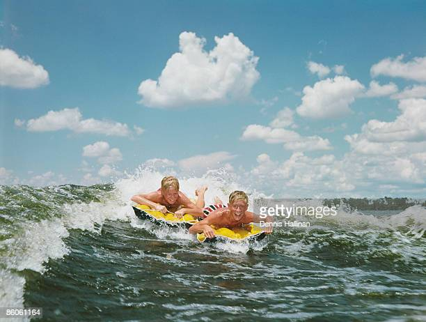 Boys riding waves on inflatable rafts