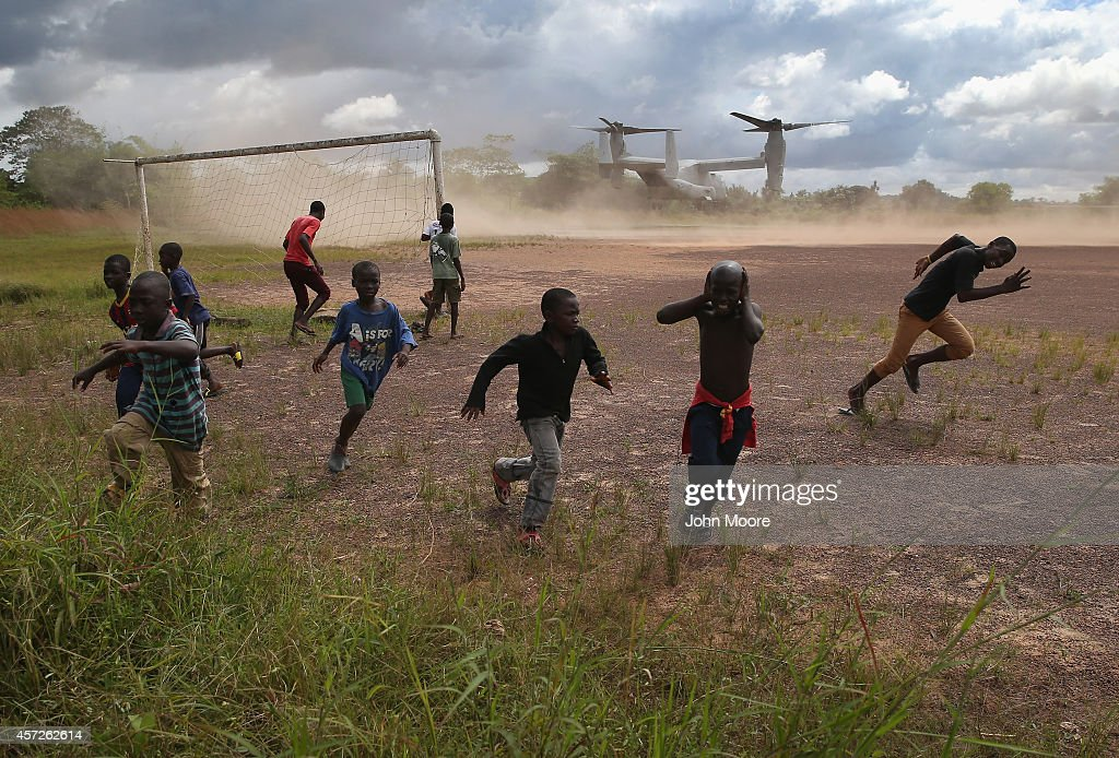 Boys run from the blowing dust as a US Marine MV22 Osprey tiltrotor departs the site of an Ebola treatment center under construction on October 15...