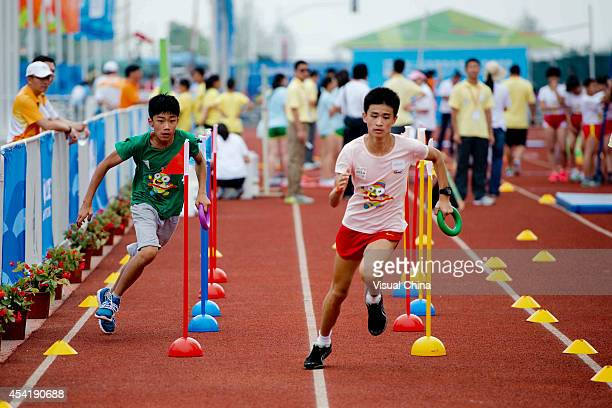 Boys run in the relay race during the IAAF Kids Athletics Program at Yanshan Road on August 26 2014 in Nanjing China