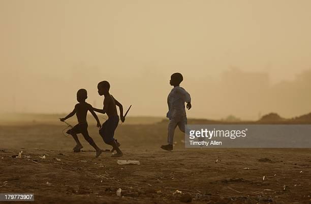 Boys running across desert, Djenne, Mali