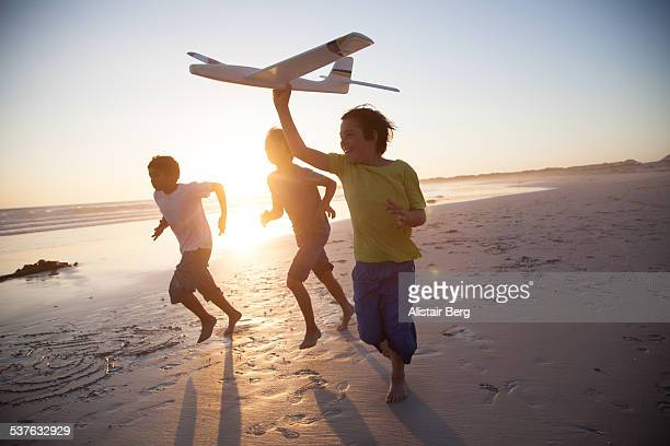 Boys running along beach with a toy plane