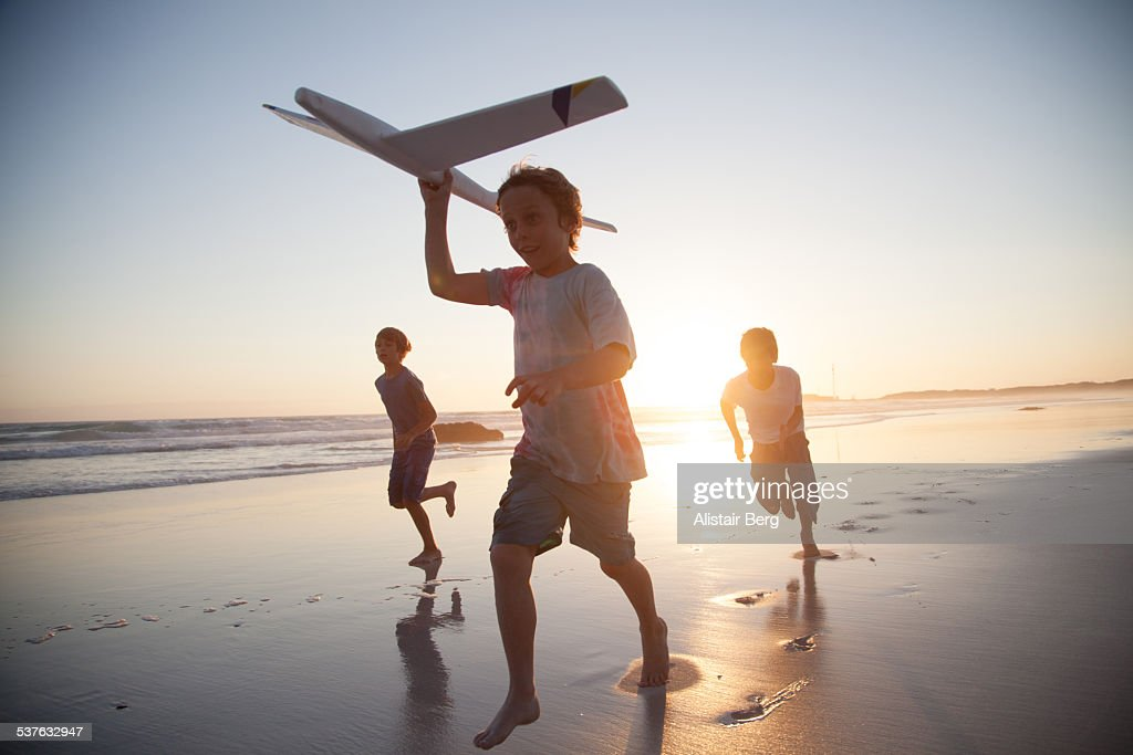 Boys running along beach with a toy plane : Stock-Foto