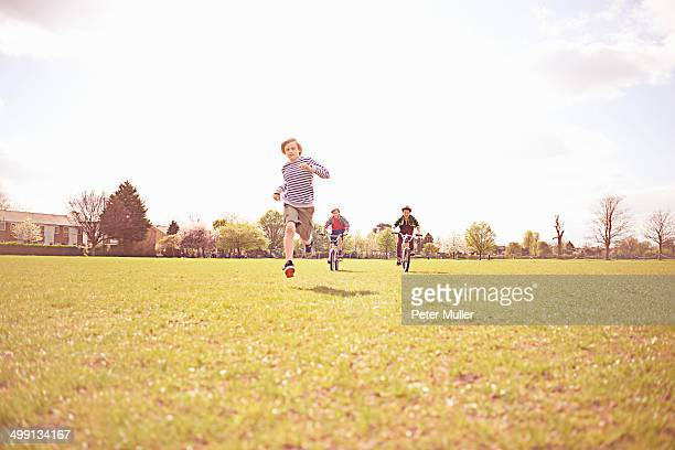 Boys running and cycling on playing field