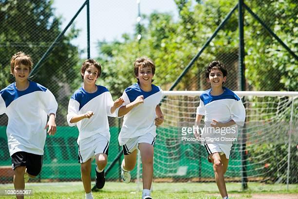 Boys running on soccer field