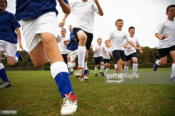 Boys (9-11) running on soccer field