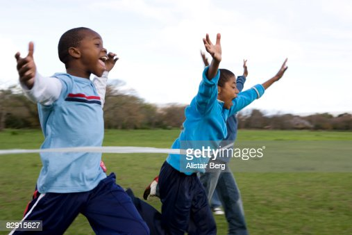 Boys running through finishing line : Stock Photo