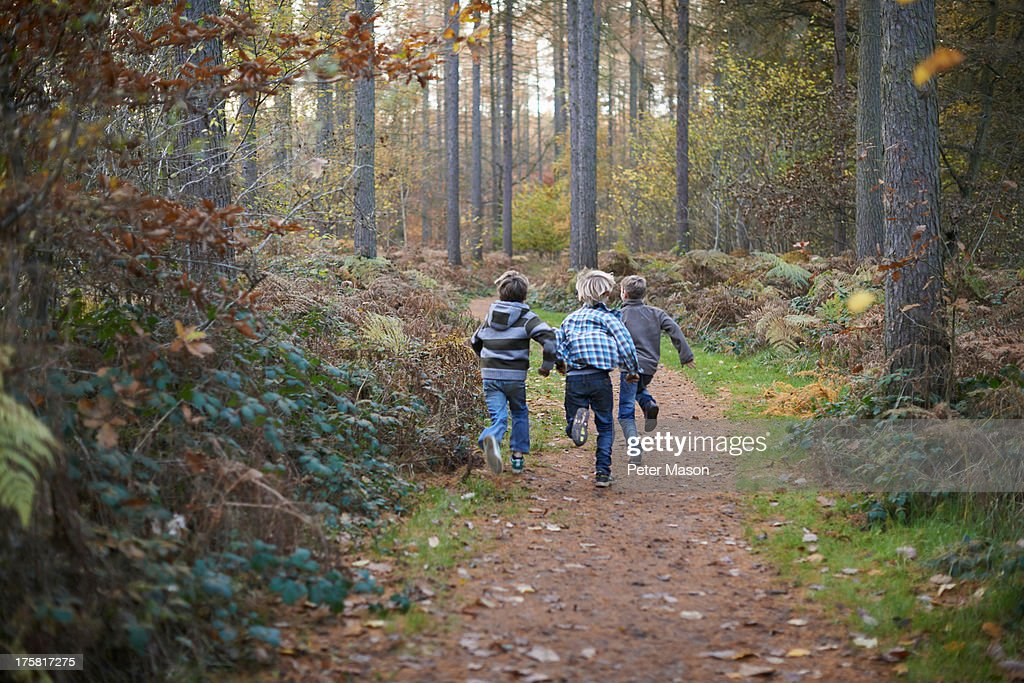 Boys running through forest