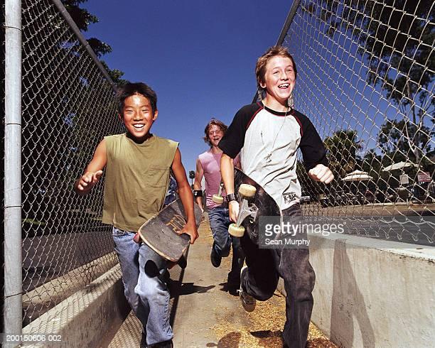 Boys (11-15) running with skateboards, portrait