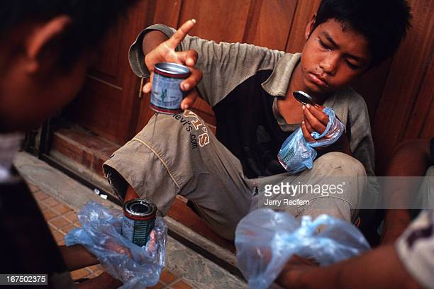Boys share a can of glue they pooled their money to buy They will all get high sniffing the glue fumes from plastic bags They are part of about 20...