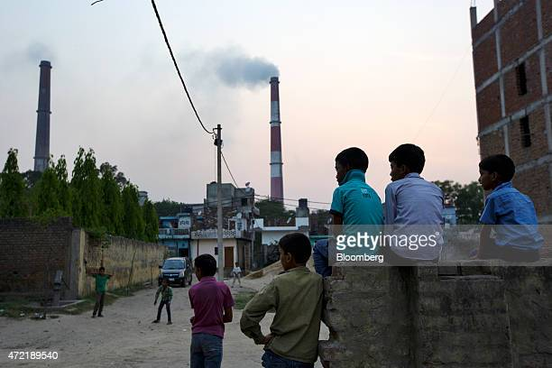 Boys sit watching street cricket as emissions billow from smokestacks at the NTPC Ltd Badarpur coalfired power plant near residential property in...