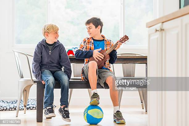 Boys siting on bench with ukulele and soccer ball