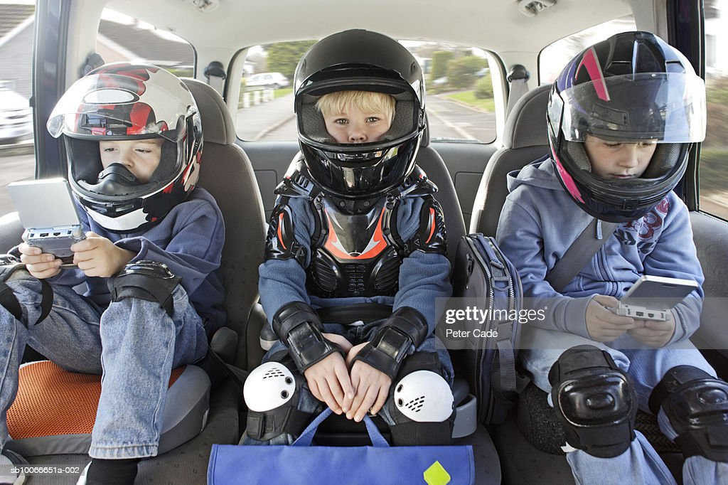 Boys (6-11) sitting in car wearing helmets