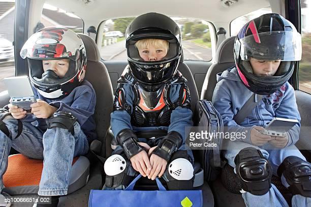 Boys (6-11) sitting in car wearing helmets