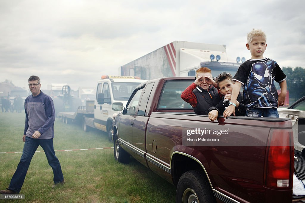 3 boys sitting in the back of a pickup truck, enjoying the Tractor Pulling Event as a man walks by. The haziness is due to a motor being started and burning too much oil.