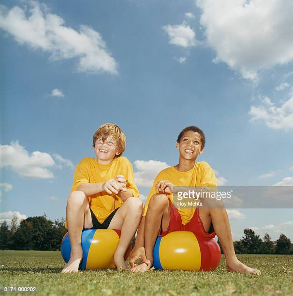 Boys Sitting on Beach Balls