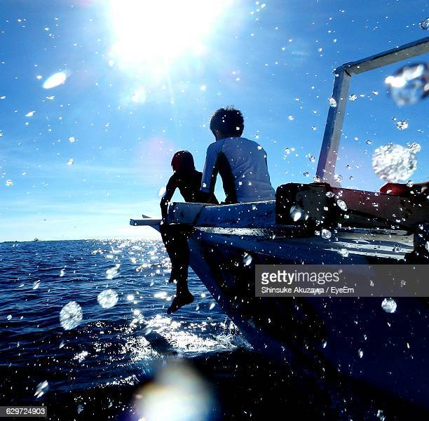 Boys Sitting On Boat In Sea During Sunny Day