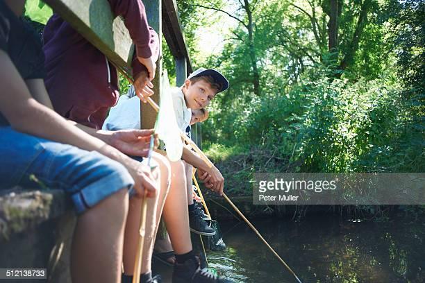 Boys sitting on bridge, fishing