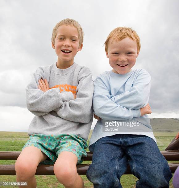 Boys (5-11) sitting on fence rail, portrait
