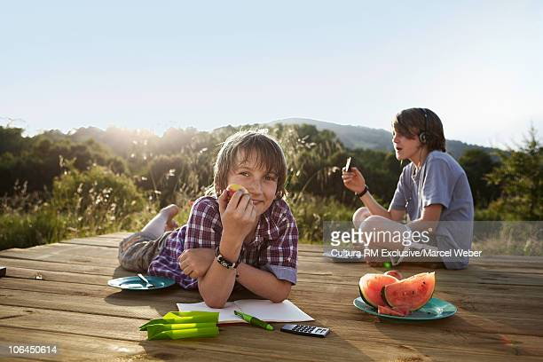 Boys sitting on patio eating apple