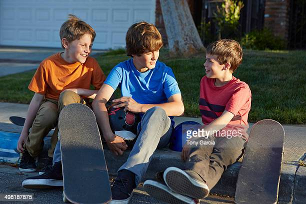 Boys sitting on pavement with skateboards