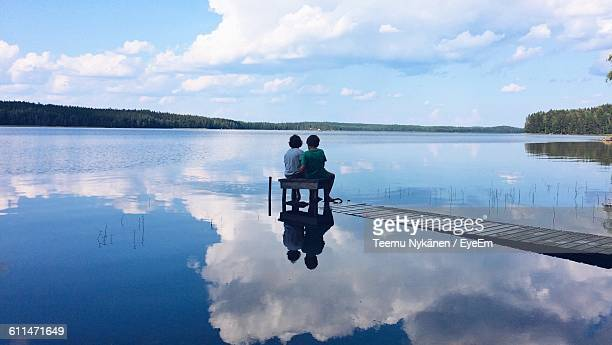 Boys Sitting On Pier At Lake Against Sky
