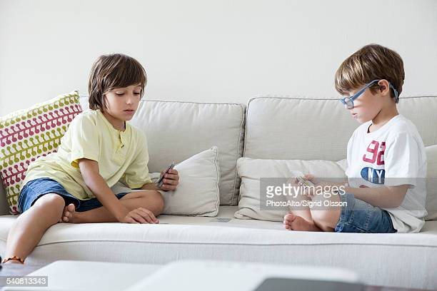Boys sitting on sofa playing cards