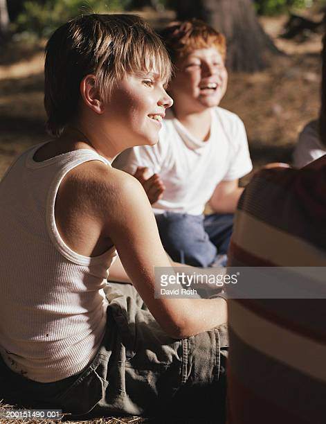 Boys (9-11) sitting outdoors, laughing